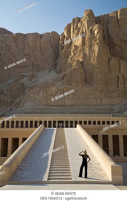 Woman tourist gazes at the Temple of Hapshetsu, Nile Valley, Egypt