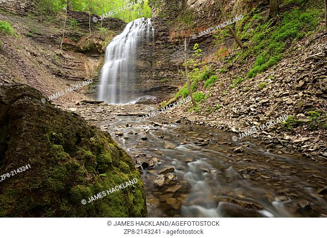 A large boulder sits in a creek with Tiffany Falls in the background in Ancaster, Ontario Canada