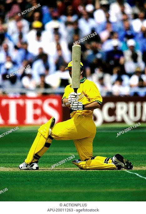 Cricketer swinging bat in cricket match