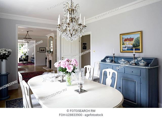 Glass chandelier above white painted table and chairs in Gustavian style dining room with antique Swedish sideboard