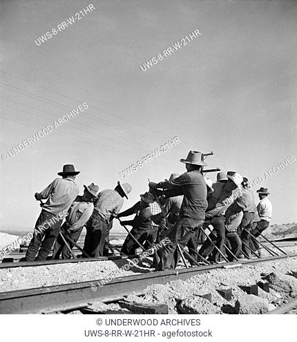Needles, California: March, 1943 An Indian section gang at work on the tracks in the Atchison, Topeka and Santa Fe Railroad yards