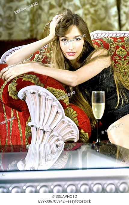 beautiful young rich woman near a coffee table with glass of fizz
