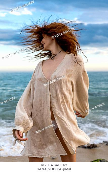 Redheaded young woman tossing her hair on the beach