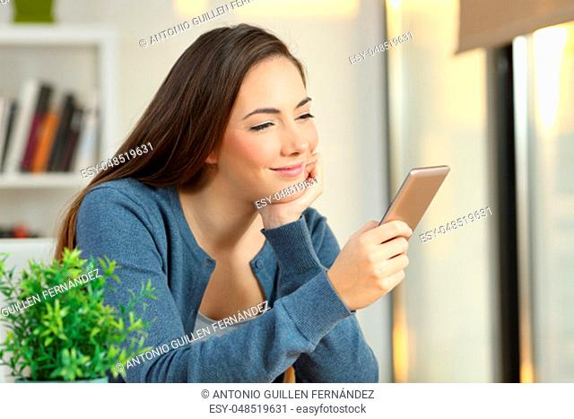 Portrait of a relaxed girl checking a smart phone at home