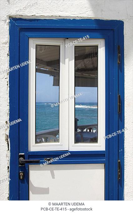 Blue doorand white wall with glass and the sea behind it