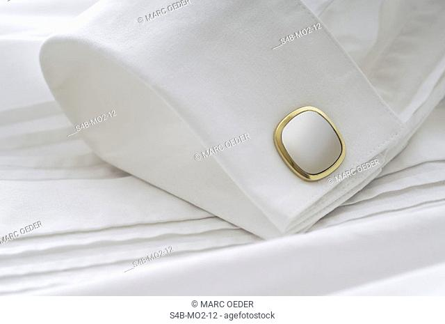 Golden cuff on the sleeve of a shirt, close-up
