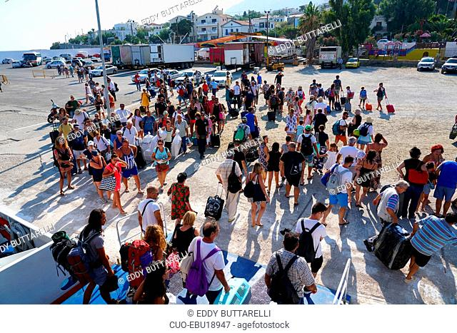 Tourists coming down from the ferry in the port of the island of Ikaria, Greece, Europe