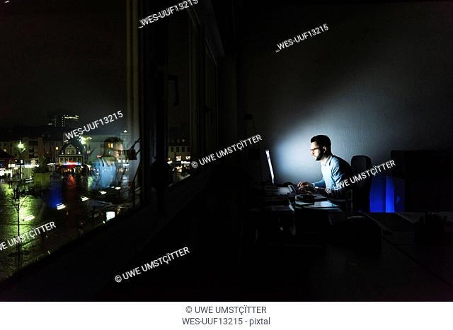 Businessman working on computer in dark office