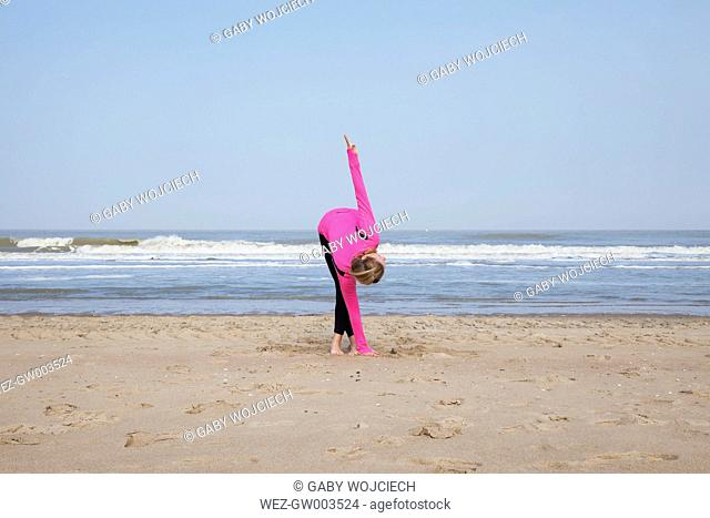 Belgium, Flanders, woman doing yoga exercise on the beach