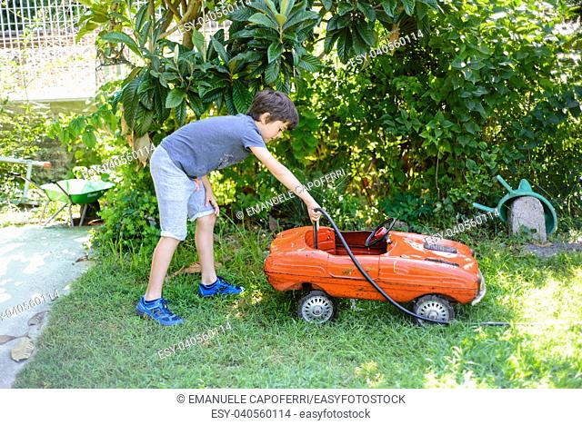 child cleans red tin toy car in the garden