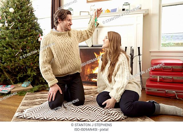 Young couple sitting on living room rug holding up christmas decoration