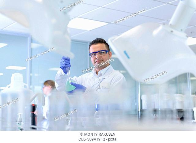 Portrait of scientist inspecting coloured samples in testing laboratory
