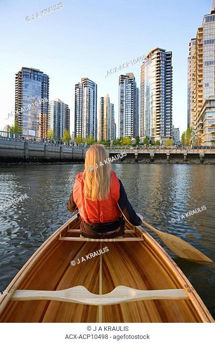 Girl paddling canoe across from downtown condominiums, False Creek, Vancouver, British Columbia, Canada