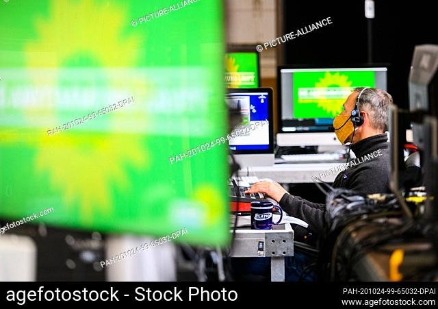 24 October 2020, Hessen, Karben: A technician sits at the mixing console in the control room at the digital party conference of Bündnis90/Die Grünen with a...