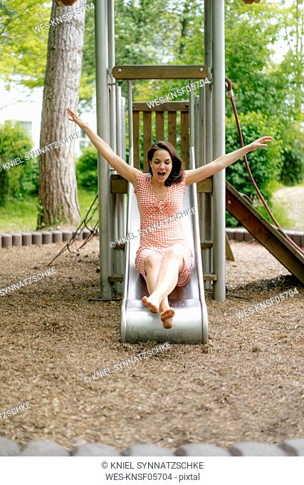 Woman sliding on a slide on a playground