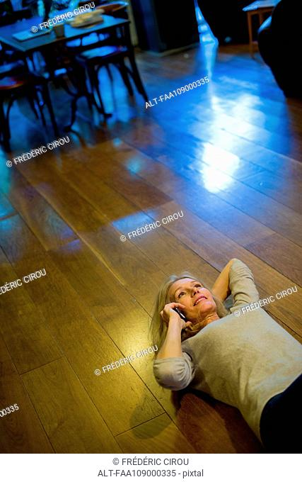Woman lying on back on floor, talking on cell phone