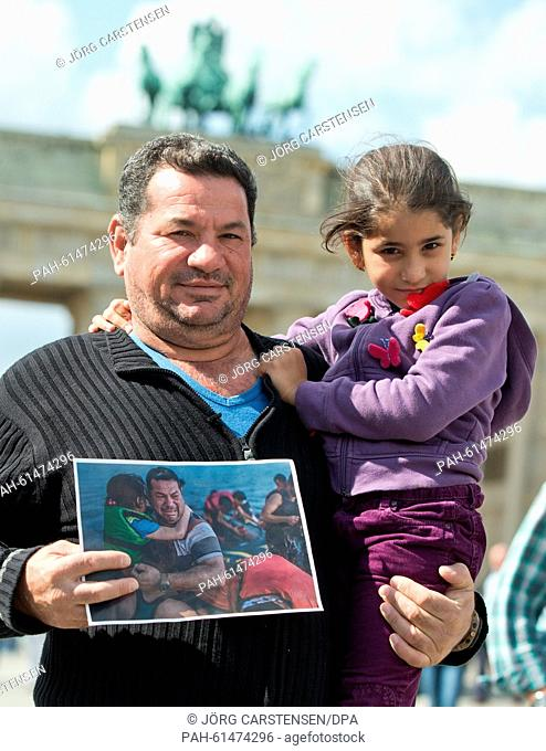 Iraqi refugee Laith Majid Al-Amirij and his 7-year-old daughter Noor pose with a photo showing them during their crossing on the Greek island of Kos