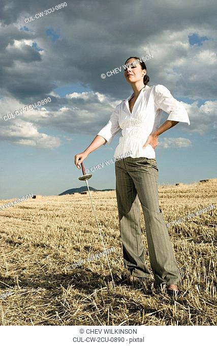 Woman standing with sword in wheat field