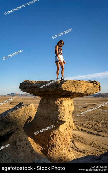 Lifestyle, slim caucasian girl portrayed in a beautiful desert on a stone, vertical photo