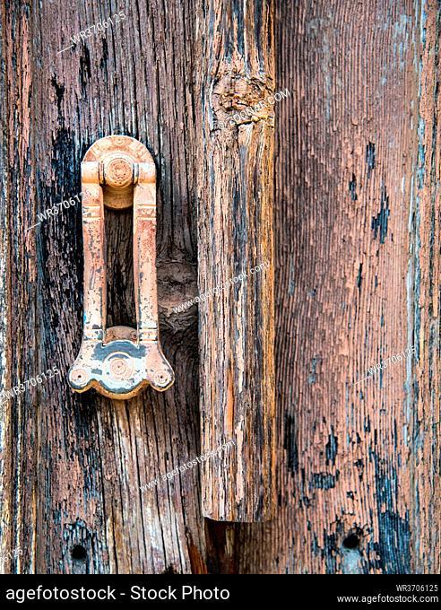 Metal vintage door handle on an old closed wooden rusty door
