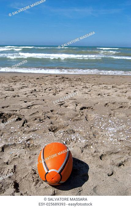 rugby ball on the beach with on the background the sea