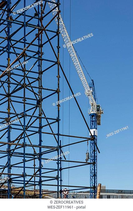 Construction crane and scaffold on construction site
