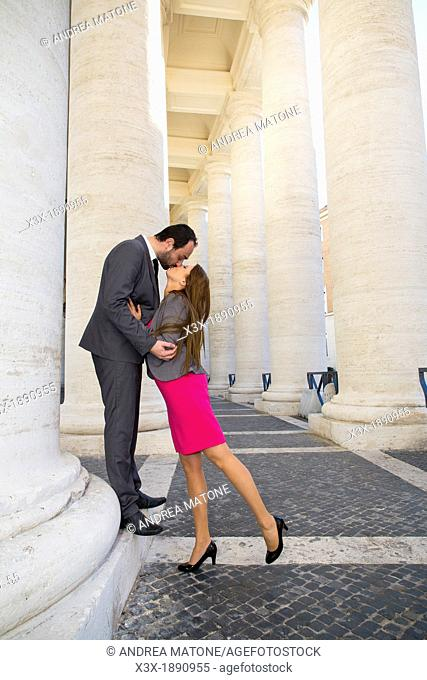 Couple kissing in the colonnade of Saint Peter's cathedral Vatican Rome Italy