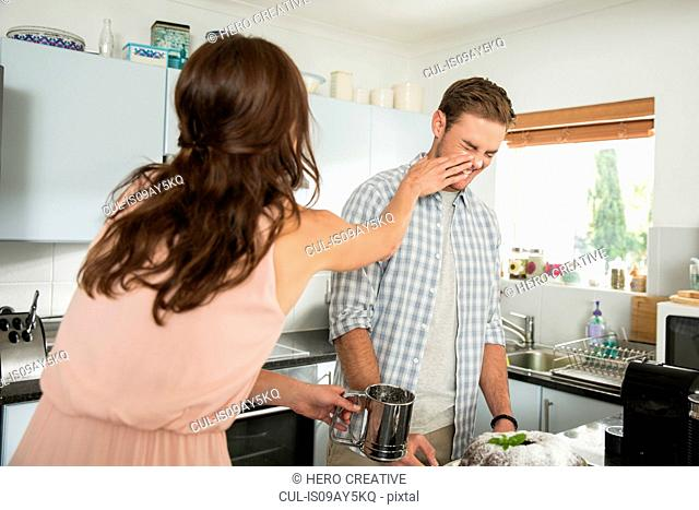 Couple playing around with icing sugar in kitchen