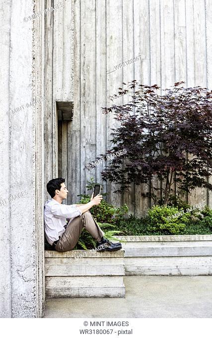 Businessman taking a break in a city park alcove
