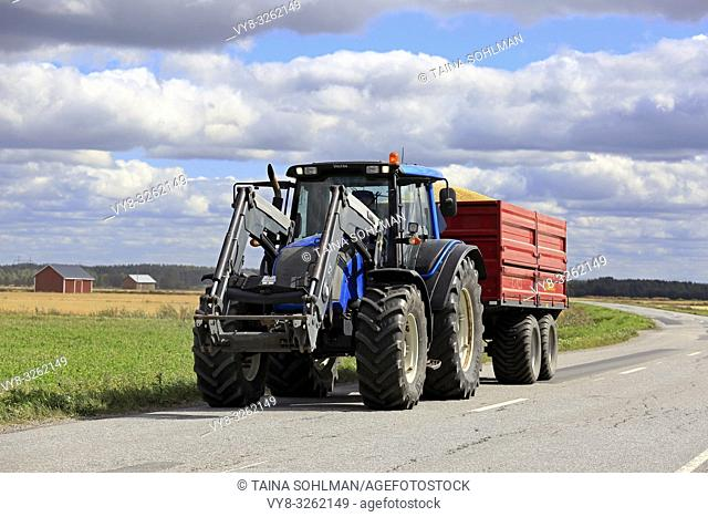 Ilmajoki, Finland - August 11, 2018: Blue Valtra farm tractor pulls trailer load of harvested grain along rural road on a clear day of autumn harvest