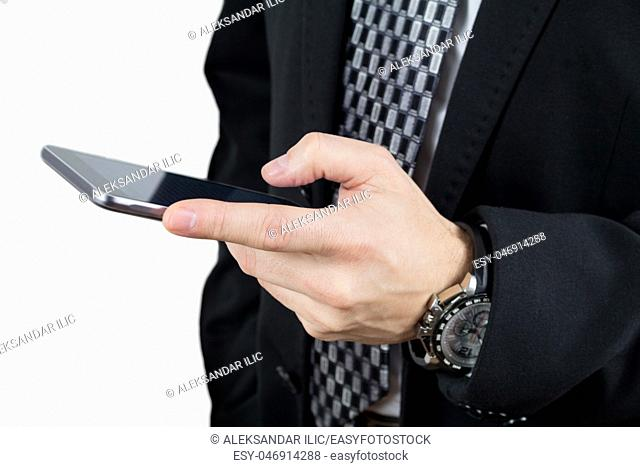 Businessman in Back Suit and Tie Holding Smartphone in Hand And Typing a Message Against White Background