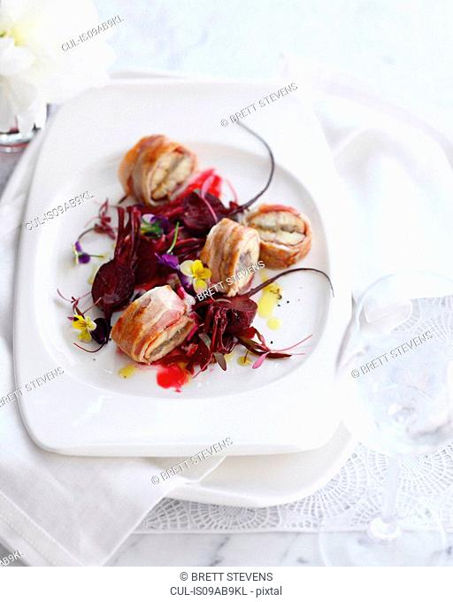 Plate of smoked eel wrapped in bacon with beetroot salad