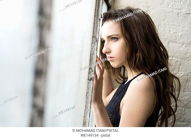 Sad young woman standing by the window