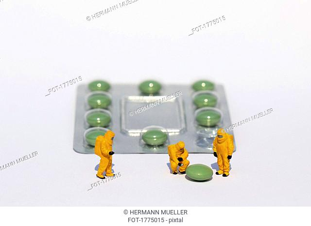 Small scientists in clean suits examining green pill from blister pack