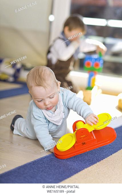 baby boy playing on floor with brother in background
