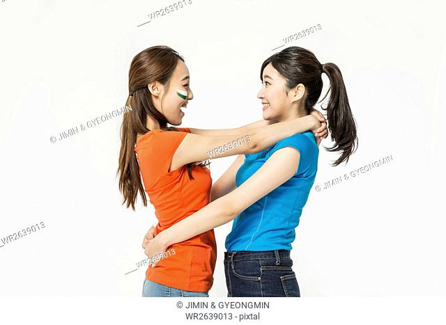 Side view of two young women hugging each other