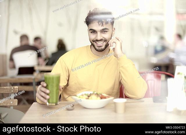Young man sitting at table in restaurant, eating salad