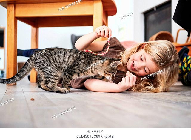 Young girl lying on floor, playing with pet cat