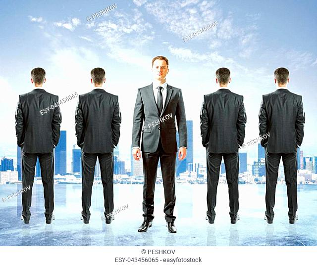 Row of businessmen with only once facing camera. City background. Leadership concept
