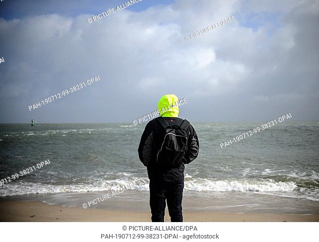 19 February 2019, Schleswig-Holstein, Sylt: A young man overlooks the sea. Sylt is the largest North Frisian island in Germany