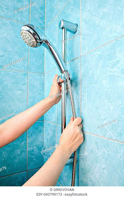 Replacing the plumbing in the bathroom, close-up human hands installed hose with shower head in height adjustable shower bar slider rail