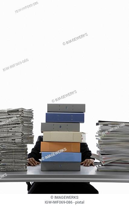Businessman sitting behind stack of binders and documents