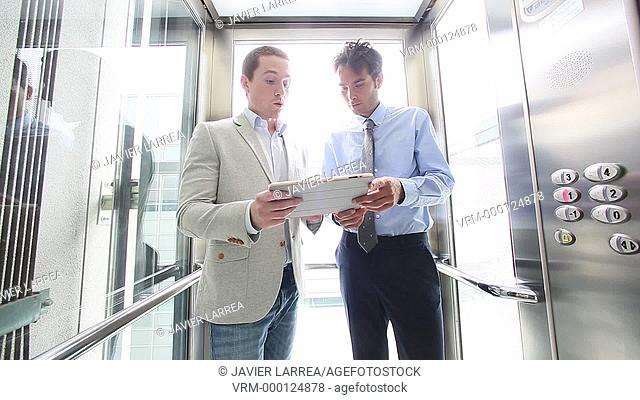 Two executive down elevator and using digital tablet , Office building, Business, San Sebastian Technology Park, Donostia, San Sebastian, Gipuzkoa