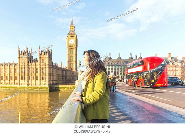 Side view of young woman on Westminster bridge, looking away, Thames river, London, UK