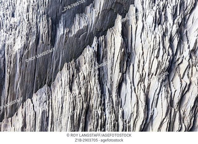 Shale-like rock depositions at the base of the cliffs on Reynisfjara beach in Iceland
