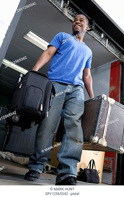 Young man carrying suitcase and smiling