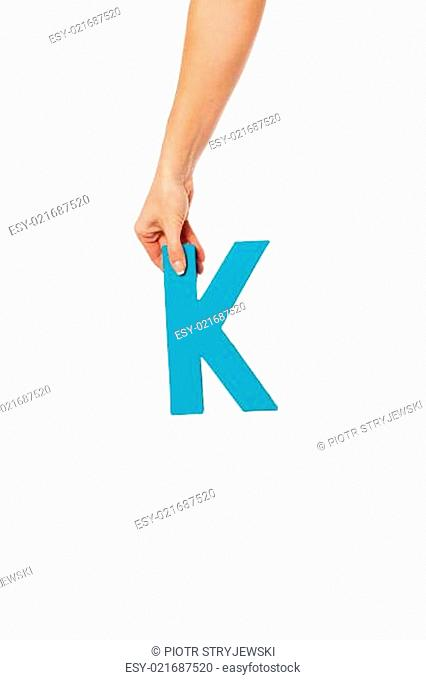 hand holding up the letter K from the top