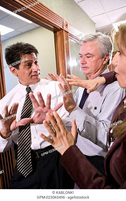 Three Multi-ethnic businesspeople having discussion in office corridor