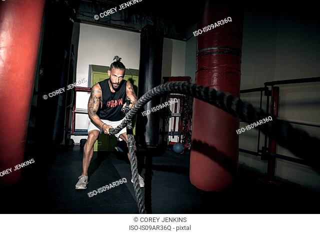 Male boxer doing battle rope training in gym