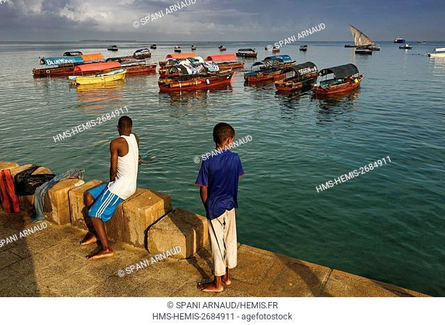 Tanzania, Zanzibar, Zanzibar City, Stone Town, listed as World Heritage by UNESCO, children on the edge of a seaside pier